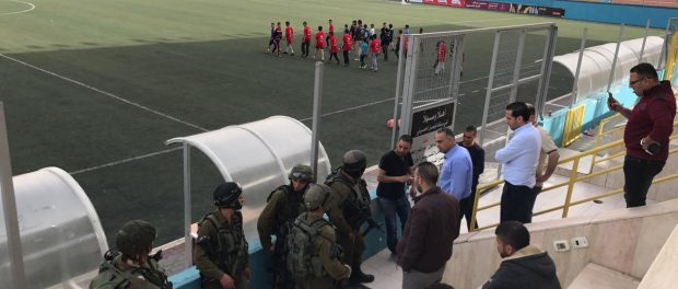 Israeli troops penetrate the Palestinian national stadium, with guns at the ready.